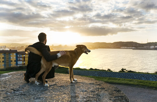 Spain, Gijon, man and his dog at evening twilight - MGOF001620
