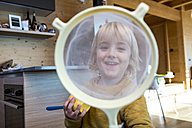 Portrait of smiling little boy looking through strainer in the kitchen - ZOCF000010