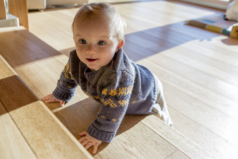 Portrait of baby boy leaning on wooden steps at home - ZOCF000013