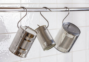 Three preserve cans hanging on meat hooks - WDF003577
