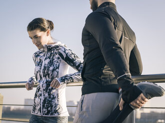 Germany, Cologne, Young couple worming up for workout - MADF000864