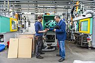 Manager and worker in plastics factory discussing production quality - DIGF000112