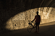 Silhouette of racing biker standing in a tunnel - JASF000557