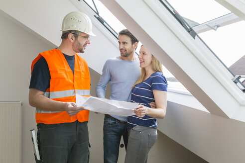 Construction worker and couple discussing rebuilding of their new home - SHKF000542