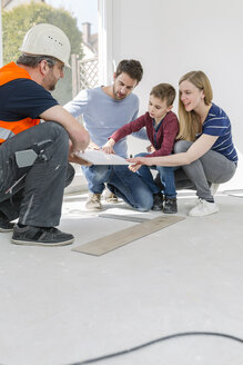 Construction worker showing family tile samples - SHKF000551