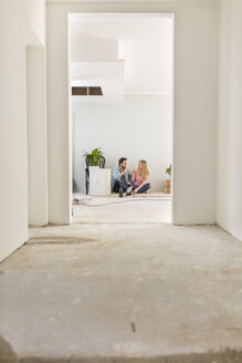 Celebrating couple sitting on the floor of their unfinished new home - SHKF000563