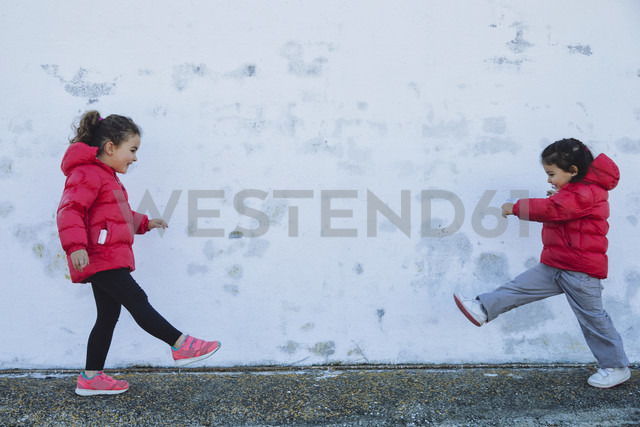 Two little girls playing in front of a wall - ERLF000152 - Enrique Ramos/Westend61