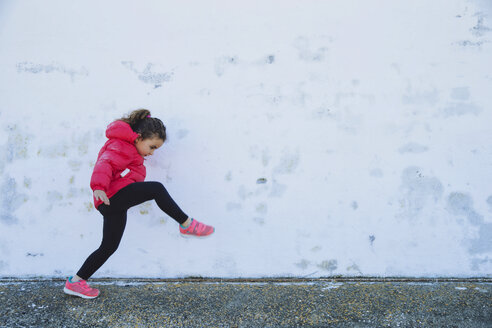 Little girl marching in front of a wall - ERLF000155