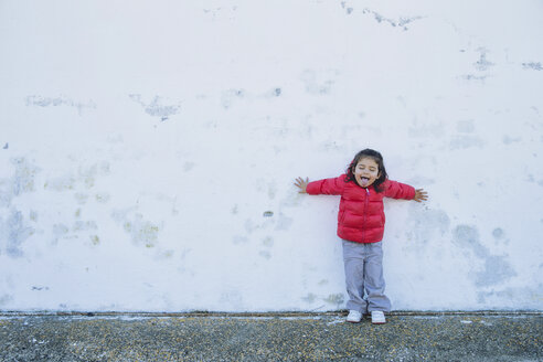 Portrait of little girl leaning against with outstretched arms sticking out tongue - ERLF000158