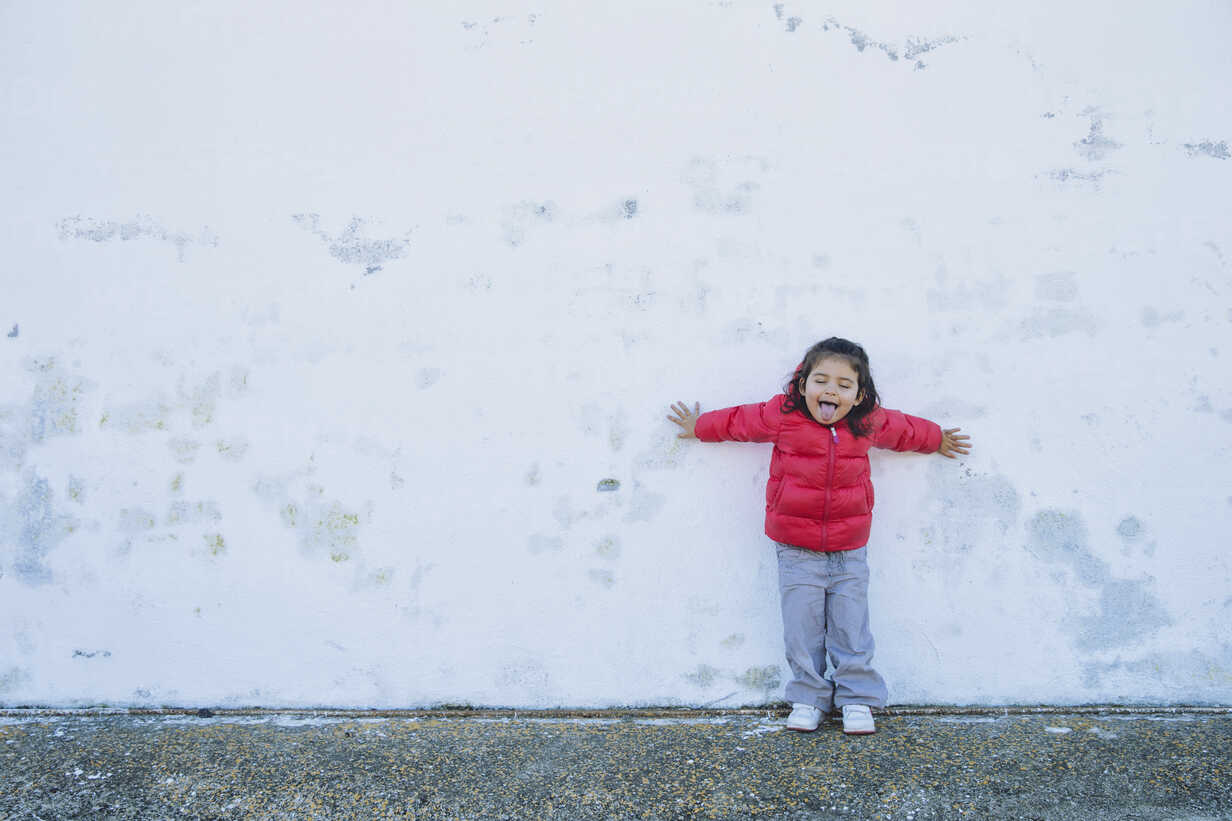 Portrait of little girl leaning against with outstretched arms sticking out tongue - ERLF000158 - Enrique Ramos/Westend61