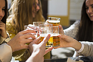 Friends toasting with beer glasses in a street cafe, close-up - KIJF000245