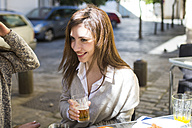 Portrait of young woman drinking beer in a street cafe - KIJF000248