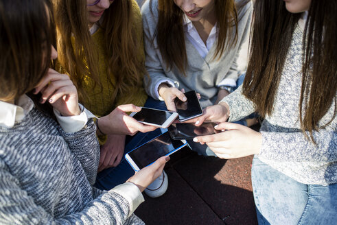Four young women comparing her smartphones - KIJF000254