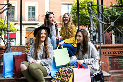 Group picture of four friends with  shopping bags - KIJF000260