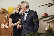 Senior couple holding bottle of Champagne on New Yera's Eve - MFF002919