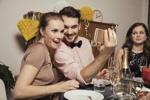 Friends taking selfies with smart phone on New Year's Eve - MFF002934