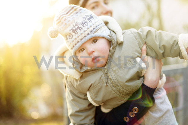 Portrait of baby girl holding by her mother's arm - BRF001296