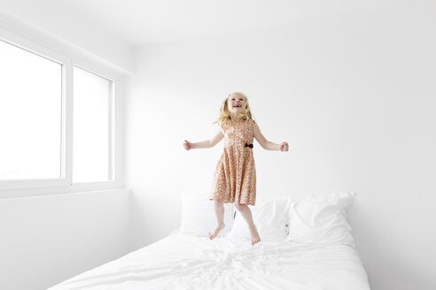 Laughing little girl wearing summer dress jumping on a white bed - LITF000193