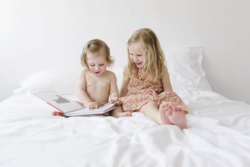 Two little sisters sitting on a white bed watching picture book - LIT000217