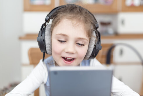 Portrait of little girl with headphones  watching something on digital tablet - OPF000109
