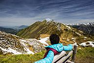 Germany, Bavaria, Allgaeu, woman sitting on bench, view to Felhorn near Oberstdorf - WGF000840