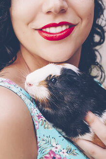 Back view of young woman with Guinea pig on her shoulder - RTBF000051