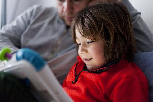 Happy little boy llooking at digital tablet - VABF000382