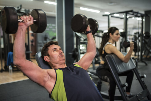 Mature couple training in gym, man doing pectoral muscle exercises and woman biceps exercises - JASF000572