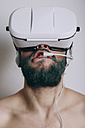 Shirtless man wearing Virtual Reality Glasses and headset biting his lip - RTBF000057