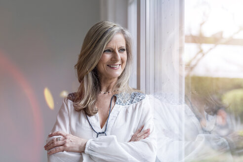 Portrait of smiling blond woman with arms crossed looking through window - SHKF000589