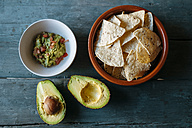 Sliced avocado and bowls of nacho and guacamole - KIJF000280