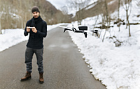 Spain, Asturias, man navigating a drone in the snowy mountains - MGOF001627