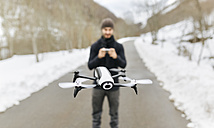 Spain, Asturias, man navigating a drone in the snowy mountains - MGOF001630