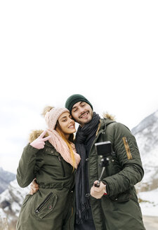 Spain, Asturias, couple taking selfie in the snowy mountains - MGOF001642