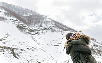 Spain, Asturias, couple hugging each other in the snowy mountains - MGOF001645