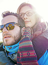 Germany, Stuttgart, portrait of young couple at backlight with reflecting of burial chapel on sunglasses - LAF001625