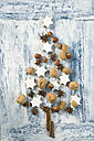 Cinnamon stars, cinnamon sticks, star anise and nuts shaped like a Christmas tree - ASF005869