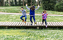Three children jumping in a park - MGOF001651