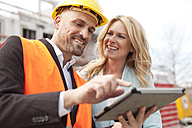 Smiling man with hard hat talking to woman on construction site - MAEF011389