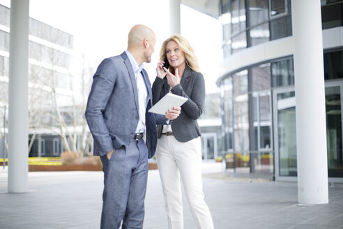 Businessman and businesswoman with digital tablet and cell phone outdoors - MAEF011404