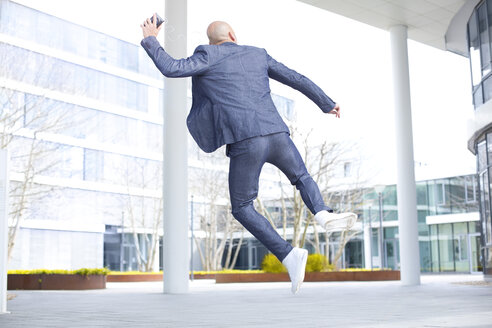 Enthusiastic businessman listening to music from smartphone and jumping mid-air - MAEF011410