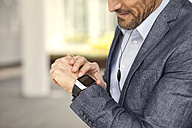 Close-up of businessman looking at smartwatch - MAEF011416