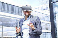 Man wearing virtual reality glasses outdoors - MAEF011422