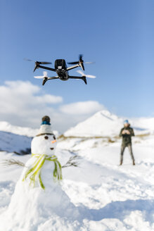 Spain, Asturias, man flying drone in snowy mountains - MGOF001677