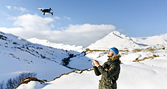 Spain, Asturias, man flying drone in snowy mountains - MGOF001680