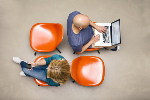 Man and woman sitting on chairs using portable devices - MAEF011424