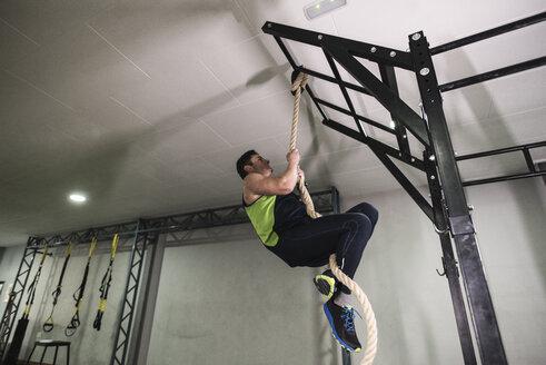 Mature man climbing rope in gym - JASF000603
