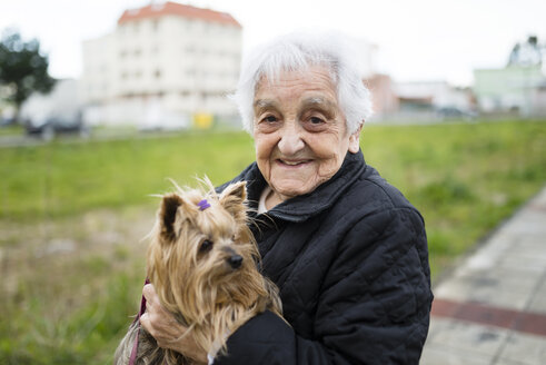 Portrait of senior woman with Yorkshire Terrier on her arms - RAEF000972