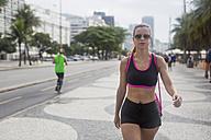 Brazil, Rio de Janeiro, sportive woman walking on pavement - MAUF000371