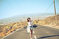Spain, teenage girl with longboard walking on empty road - SIPF000293